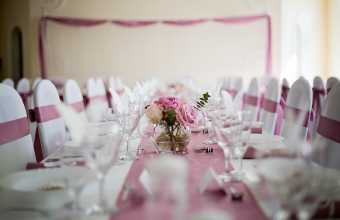 wedding table in pink and white, with roses flower center piece, empty glasses and plates, wedding reception.